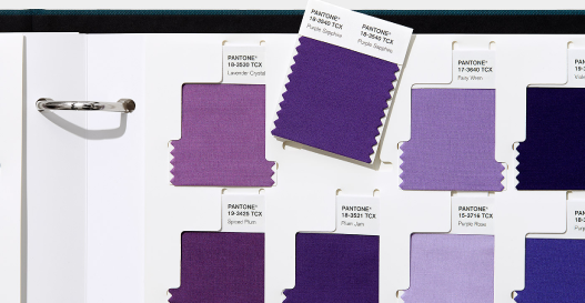 A physical Pantone swatch book showing shades of purple, lilac, plum and more.